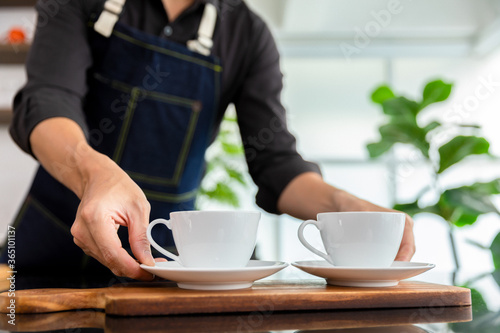 Obraz Barista pouring black coffee to white cup for service in coffee shop. - fototapety do salonu