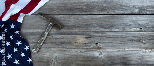 Photo Waving US flag with vintage construction hammer on weathered wooden background