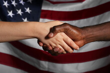 Caucasian Woman And African-American Man Shaking Hands Near National Flag Of USA. Racism Concept