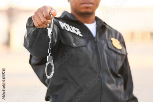 African-American police officer with handcuffs outdoors Canvas Print