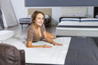 Portrait of attractive girl testing quality of new mattress for bed in salon .