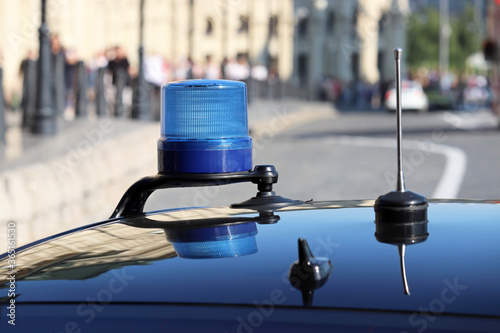 Blue flashing light and communication antennas on a government car on a city street Canvas-taulu