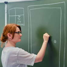 A School Teacher Is Knocking On A Chalk Painted Door. Concept Welcome Back To School