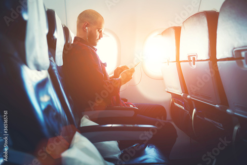 Photo Man entrepreneur is watching video on mobile phone, while is sitting in plane near window with sun rays during his business trip