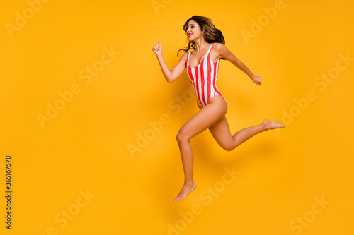 Full length body size view of her she nice attractive gorgeous chic cheerful slim slender sporty lady jumping running fast having fun isolated bright vivid shine vibrant yellow color background