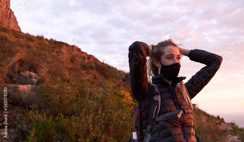 Photo Young woman adjusting face mask on top of mountain