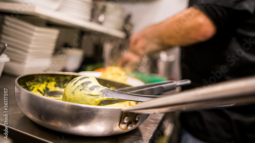 Fototapeta Primer plano de sartén en la que se ha elaborado una salsa de curry con el cocinero al fondo. obraz