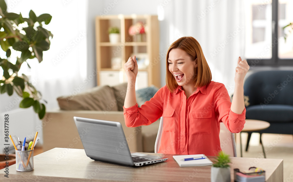 Fototapeta remote job, technology and people concept - happy smiling young woman with laptop computer working at home office and celebrating success