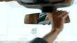 Serious woman adjusting rear view mirror. Woman sitting behind steering wheel