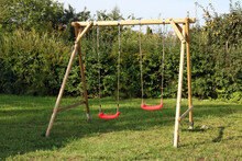 Children's Swing Made Of Logs And Ropes And Installed In The Backyard Of A Rural House
