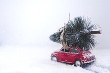 Close-up Of Red Car With Christmas Tree On Snow
