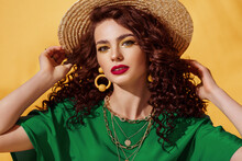 Summer Fashion Portrait Of Beautiful Curly Woman With Yellow Eyes, Fuchsia Color Lips Makeup, Wearing Trendy Earrings, Chain Necklace, Straw Hat, Green T-shirt