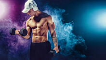 Athletic Man Training Muscles With Dumbbells In Studio On Dark Background With Smoke. Strong Bodybuilder With Six Pack, Perfect Abs, Shoulders, Biceps, Triceps And Chest Posing With Headphones.