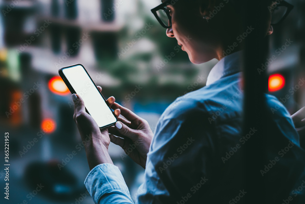 Fototapeta Back view of female person in eye glasses looking to mockup copy space screen on mobile phone.Hipster girl using blank application on smartphone device.Close up view, texting message in social network