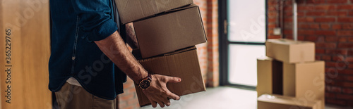 Fototapeta panoramic crop of businessman holding boxes and moving in new office obraz
