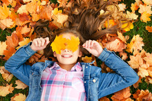 Autumn Portrait Of Happy Smiling Little Girl Child Lying In Leaves And Closing Her Eyes With Leaves In The Park