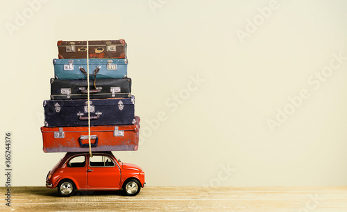 Fototapeta Suitcase on toy car roof in retro style creative travel concept. obraz