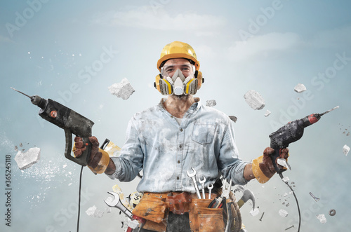 Construction worker in dirty clothes with a hammer and drill at work