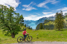 Active Senior Woman Riding Her Electric Mountain Bike Below The Seven Summits Of Churfirsten, Enjoying The Awesome View Down To Lake Walensee Canton St. Gallen, Switzerland