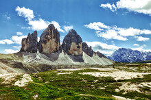 HDR Photo Of The Three Peaks Of Lavaredo, Italian Alps Mountains. Beautiful Rock Towers That Stand Out In The Sky, Small Snowfields, See Meadows, Blue Sky With Clouds.