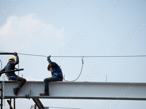 Man Working on the Working at height on construction site with blue sky