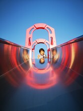 Low Angle View Of Girl On Slide In Playground Against Clear Blue Sky