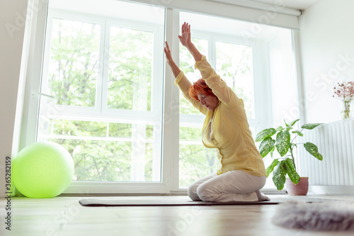 Senior woman practicing yoga at home Fototapete