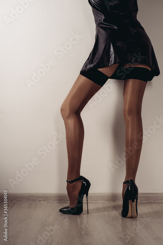 Slender female legs in stockings and a fetish shoe with extremely high heels Canvas-taulu