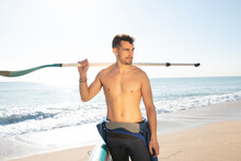 Attractive And Athlete Man  With A Paddle Surfboard On The Beach