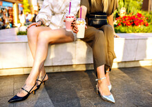 Fashion Details Of Two Woman Sitting On Marble Bench Wearing Elegant Vintage Kitten Heel Shoes Drinking Milkshakes On City Park, Focus On Long Sexy Legs Of Couple.