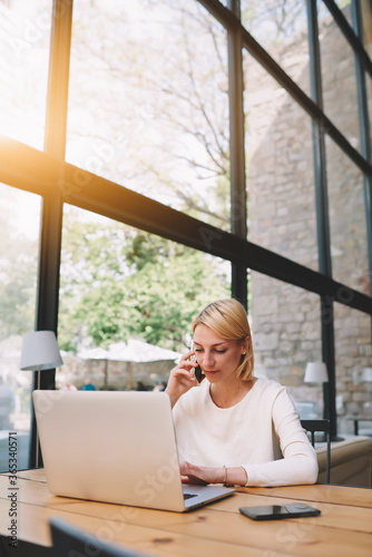 Female freelancer at distance work via internet talk on smartphone and looking to the netbook screen, young successful businesswoman busy working in modern loft office interior, flare orange sun light