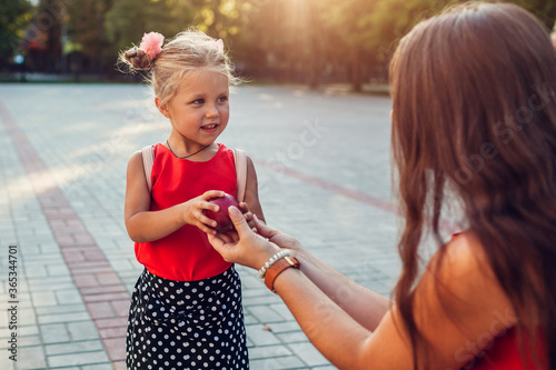 Obraz Young mother giving daughter apple outdoors primary school. Little pupil ready for lessons - fototapety do salonu