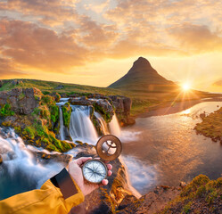 Beautiful landscape with old compass on traveler's hand. Traveling concept.