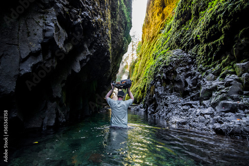 Fotografía Adventurous man holding a backpack above his head while walking through a river in a gorge