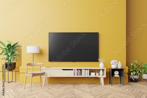 Obraz TV on cabinet in modern living room with lamp,table,flower and plant on yellow wall background. - fototapety do salonu