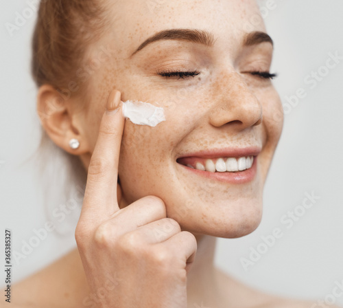 Canvas Freckled caucasian ginger lady applying on face anti aging cream and smile on a
