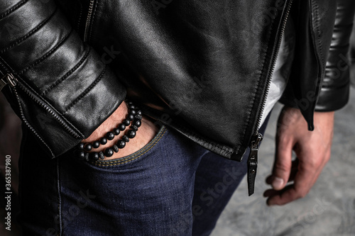 Photographie Black bracelets made of minerals and natural stones on a hand, a leather jacket, close-up