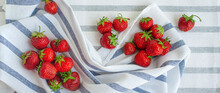Strawberries Are Scattered On Striped Towels.