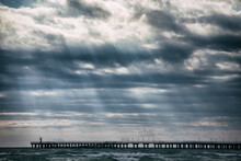 The Rays Of God Shine From The Sky To The Pier In The Sea. The Water Is Still With Waves, But Has Already Calmed Down After The Storm. The Light Calmed Everything Down.