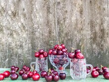 Large Ripe Red Cherries In Glass Containers On A Background Of An Abstract Wooden Surface. The Concept Of Proper Nutrition, Agriculture.Free Space.