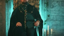 Warlike Medieval Strong Man Sits On Old Bronze Throne Holding Sword, Image Tyrannical King. Carnival Vintage Costume Velvet Clothes Royal Gold Crown, Jewelry. Serious Pensive Face. Gothic Castle Room