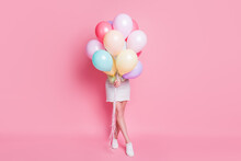 Full Size Photo Of Funny Lady Come Birthday Party Hold Many Air Balloons Hiding Face Surprise Visit Wear Casual Green Crop Pullover Jeans Skirt Shoes Isolated Pink Pastel Color Background
