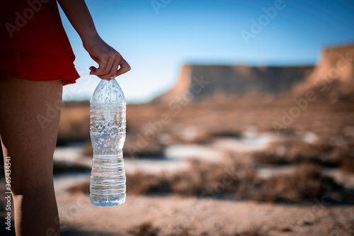 Unrecognizable woman holding unlabeled plastic water bottle on arid soil into de Wallpaper Mural