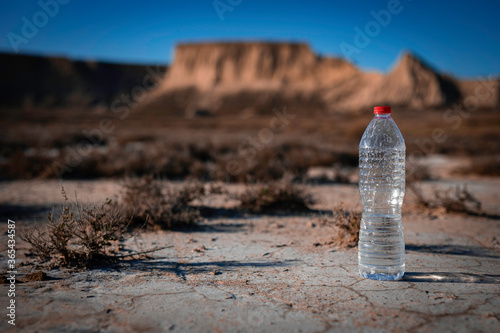 Photo Unlabeled plastic water bottle on arid soil into desertic landscape with copy sp