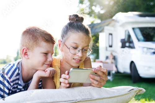 Valokuva Children with mobile phone on camping holiday