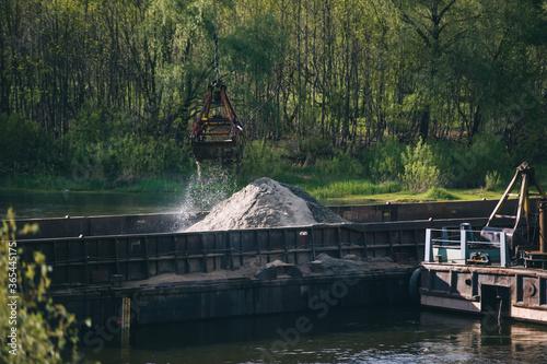 Billede på lærred Loading nitrogen fertilizers with crane on a barge on the river