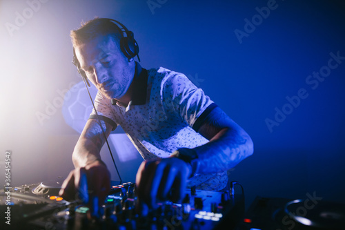 Fototapeta Techno young Caucasian male DJ with his mixer board playing music at a party