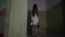 A Demonic Psycho Child In A Cursed Abandoned House. A Little Girl Dressed In A White Dress With A Bear Toy Looks Scared At The 4K Camera Footage