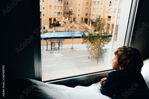 Photo Sad and melancholic boy looks through a window in his apartment during his confi