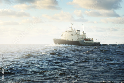 Fotografiet Soviet icebreaker in an open sea under dramatic sunset clouds